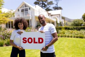 """a couple holding a """"sold"""" sign in front of a house they just bought"""