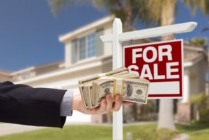 a person holding out a handful of cash in front of a house with a for sale sign in front of it